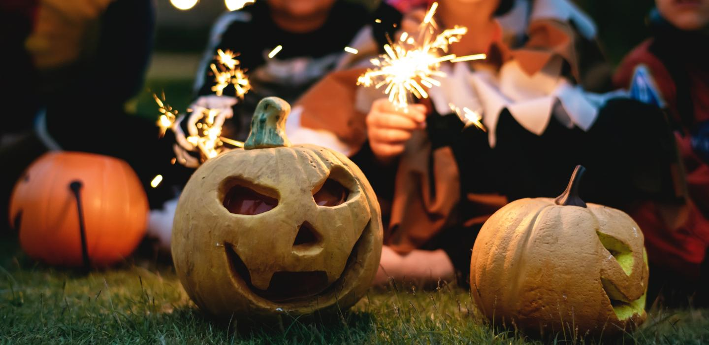 Kids with fireworks and Halloween carved pumpkins