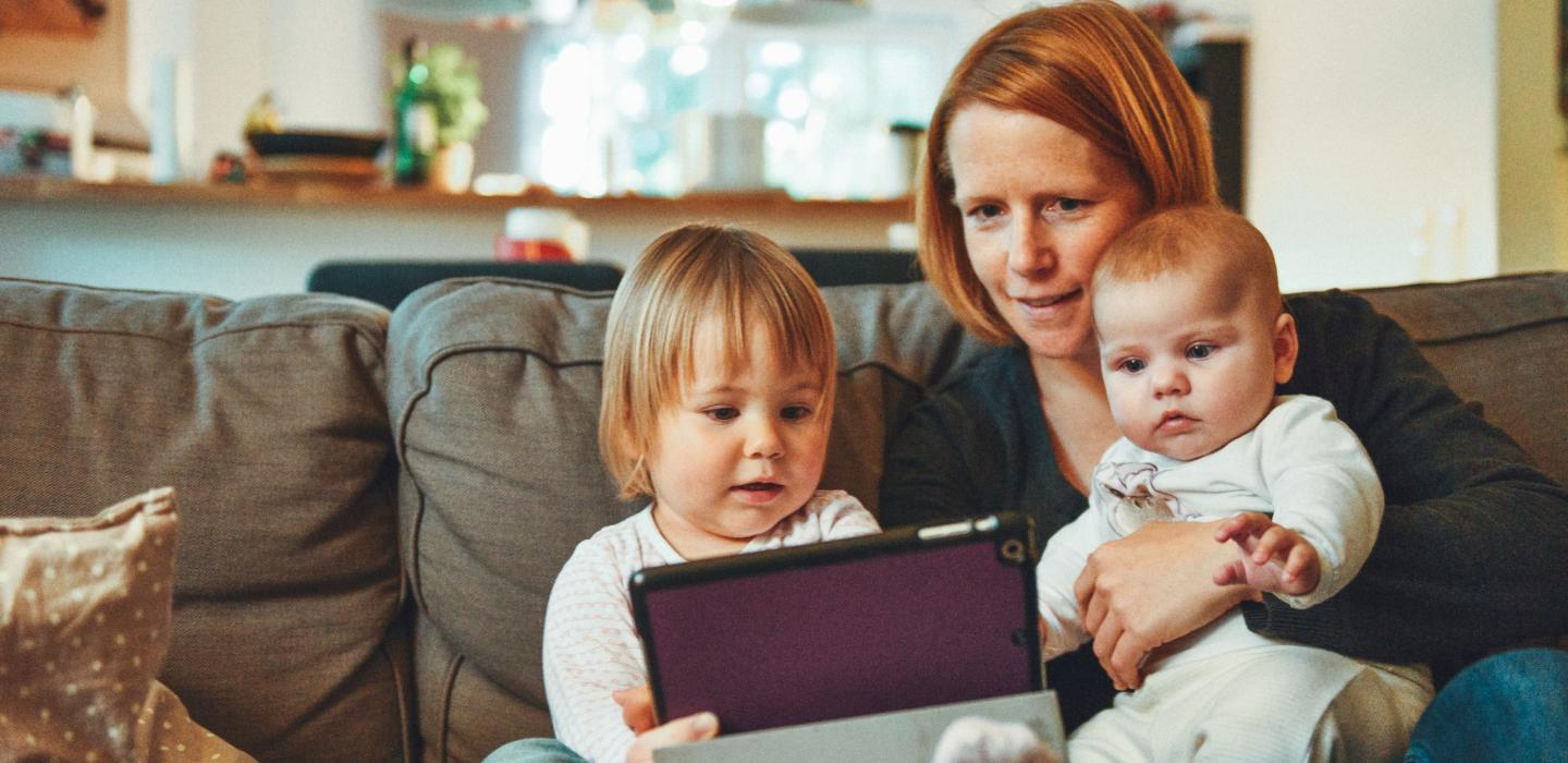 Mother with two kids on couch looking at tablet