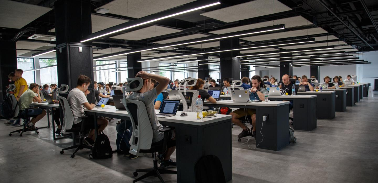 A collaborative workplace is shown with people working at their laptops