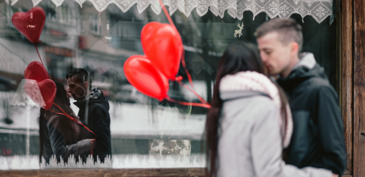 Reflection in window of couple embracing on Valentine's Day with red heart-shaped balloons
