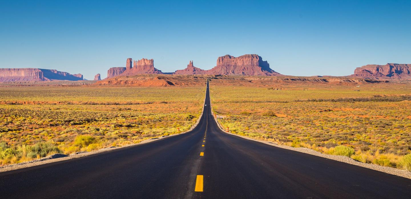 An open road with mountain ranges in Utah.