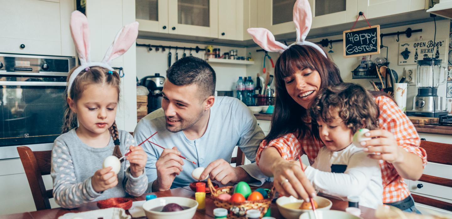 a family is painting easter eggs together at the dining table