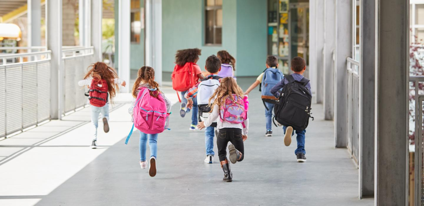 Children with backpacks running to school