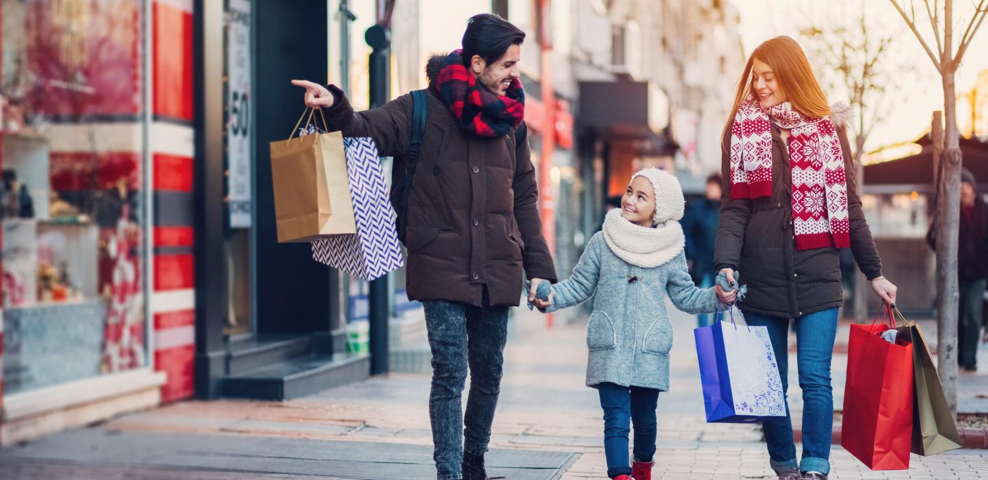 A couple and child shopping in winter