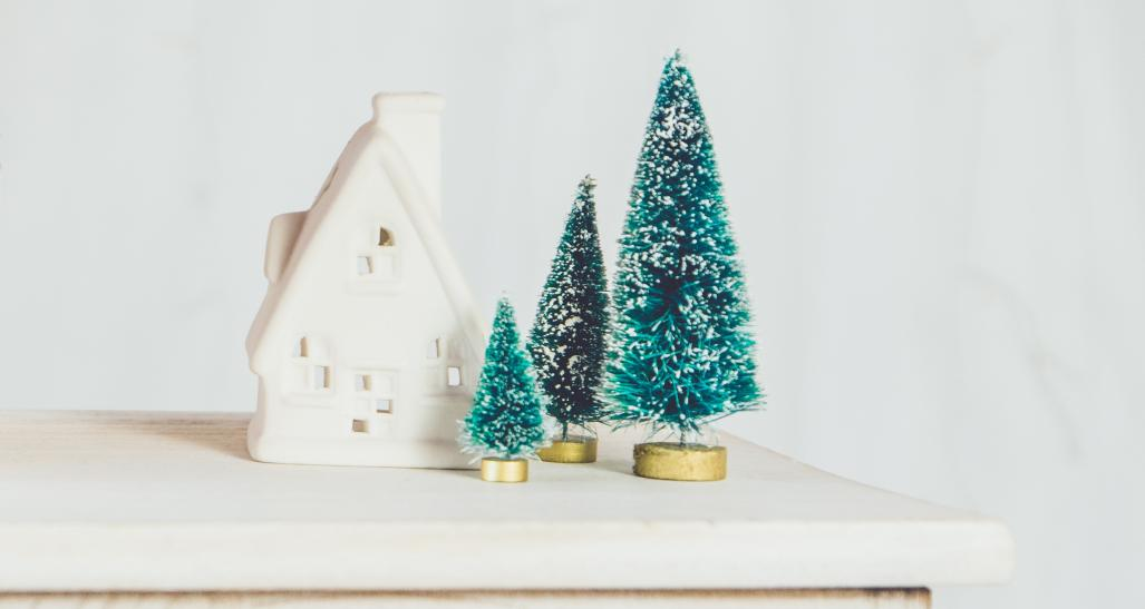 a house figurine and two small pine trees