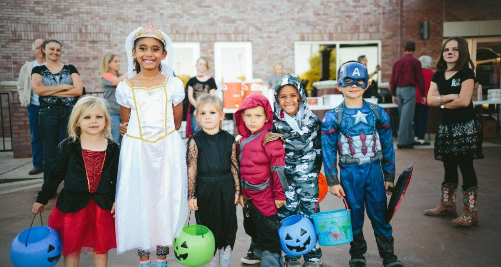 A group on children on halloween holding their candy baskets