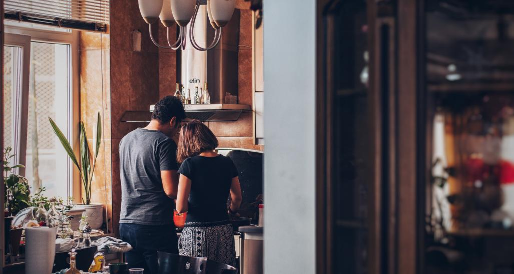 a man and a woman stand in the kitchen to prepare food