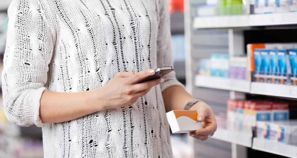 a woman in a drug store shops for medicine while looking at her mobile phone