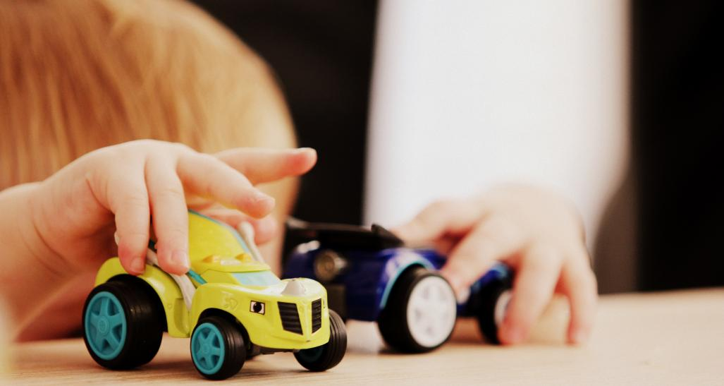 two car toys being played with by a little kid