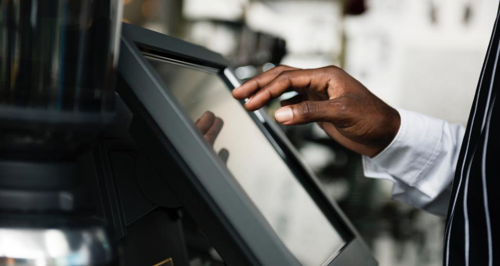 a closeup image of a cash register screen with a guys hand over it