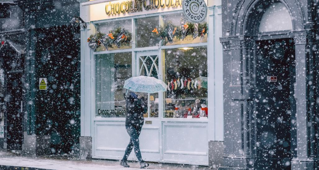 woman in a snowy town walking by stores