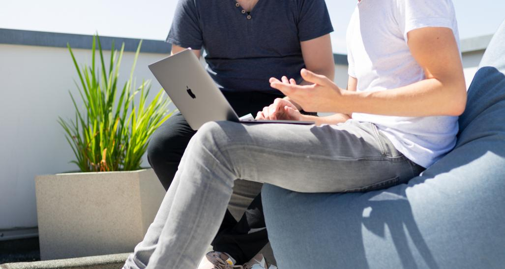 two guys sitting outside looking at a laptop together