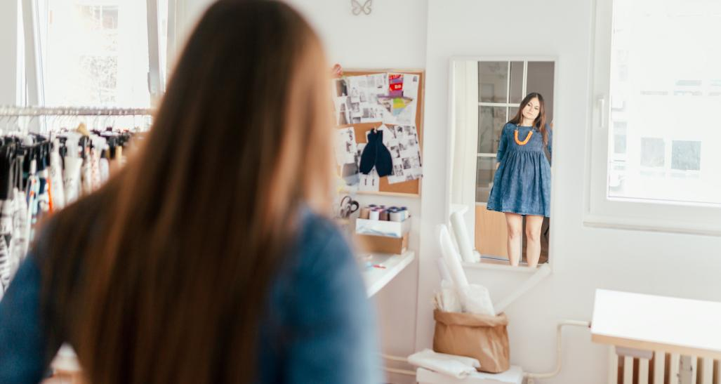 a plus size model looks in the mirror admiring her figur
