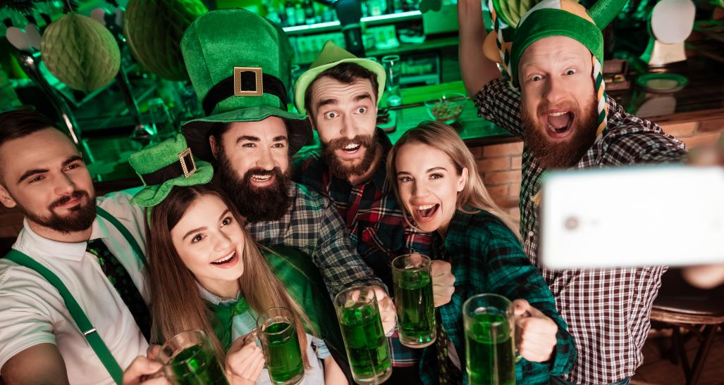 St. Patrick's Day group selfie at a bar with green beer