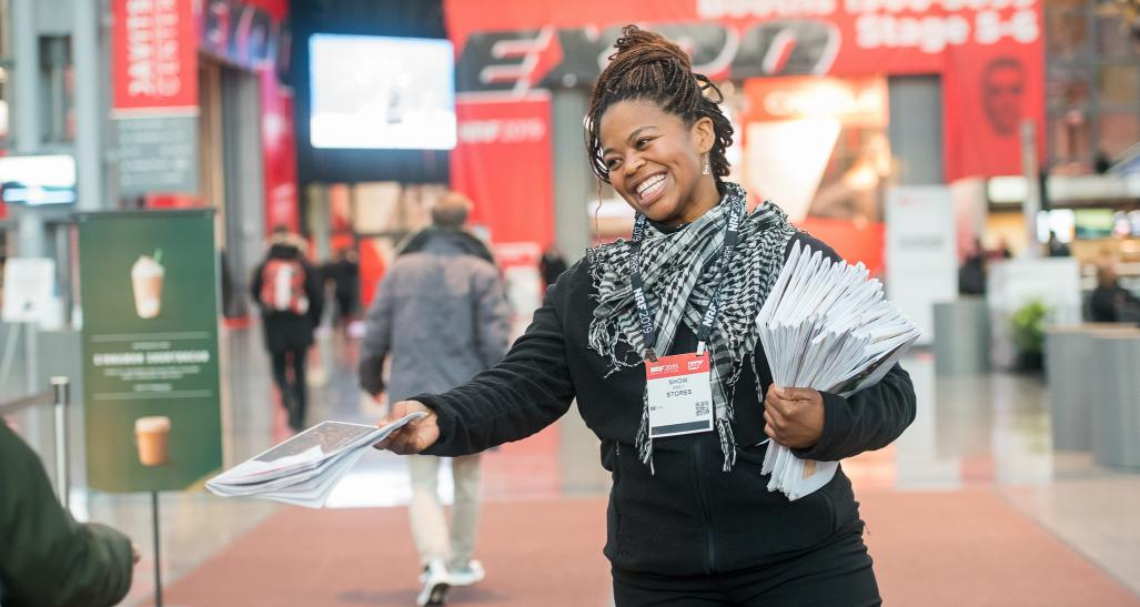 A woman is smiling while handing out pamphlets at NRF big show