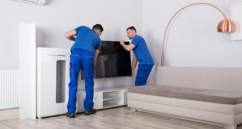 Two men delivering furniture to a living room