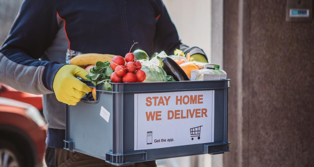 Man wearing gloves delivers box of produce