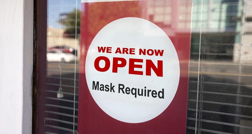 Sign on store indicating face mask required for entry