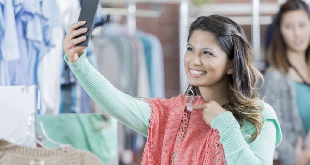 Woman takes a picture with her phone in a clothing store