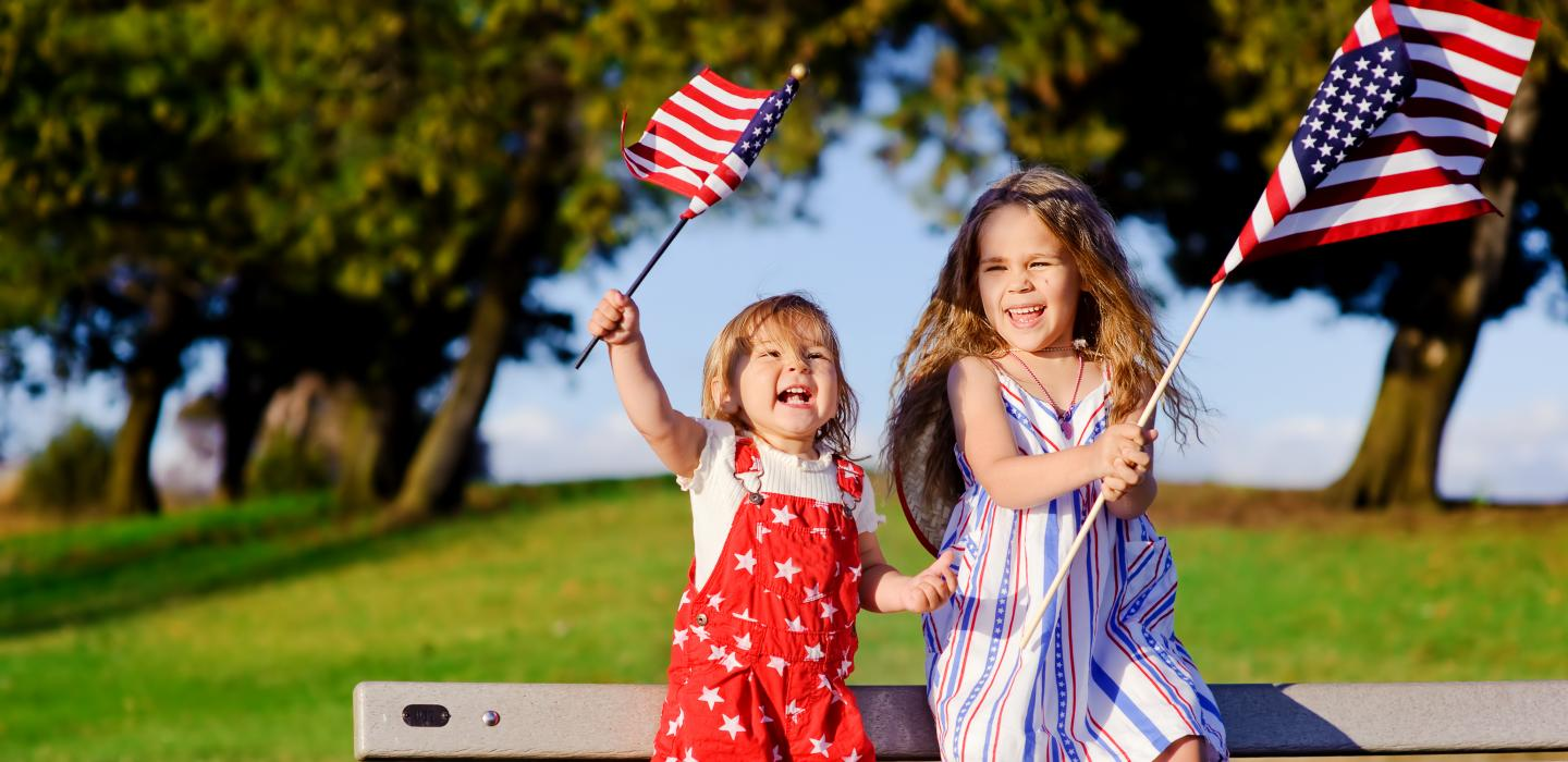 Two little girls cheer with american flags in their hands dressed for the 4th of july