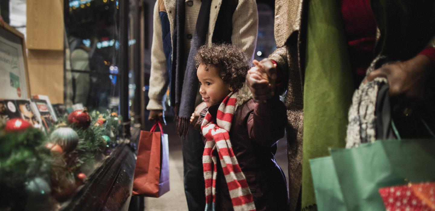 Child looks at holiday window display