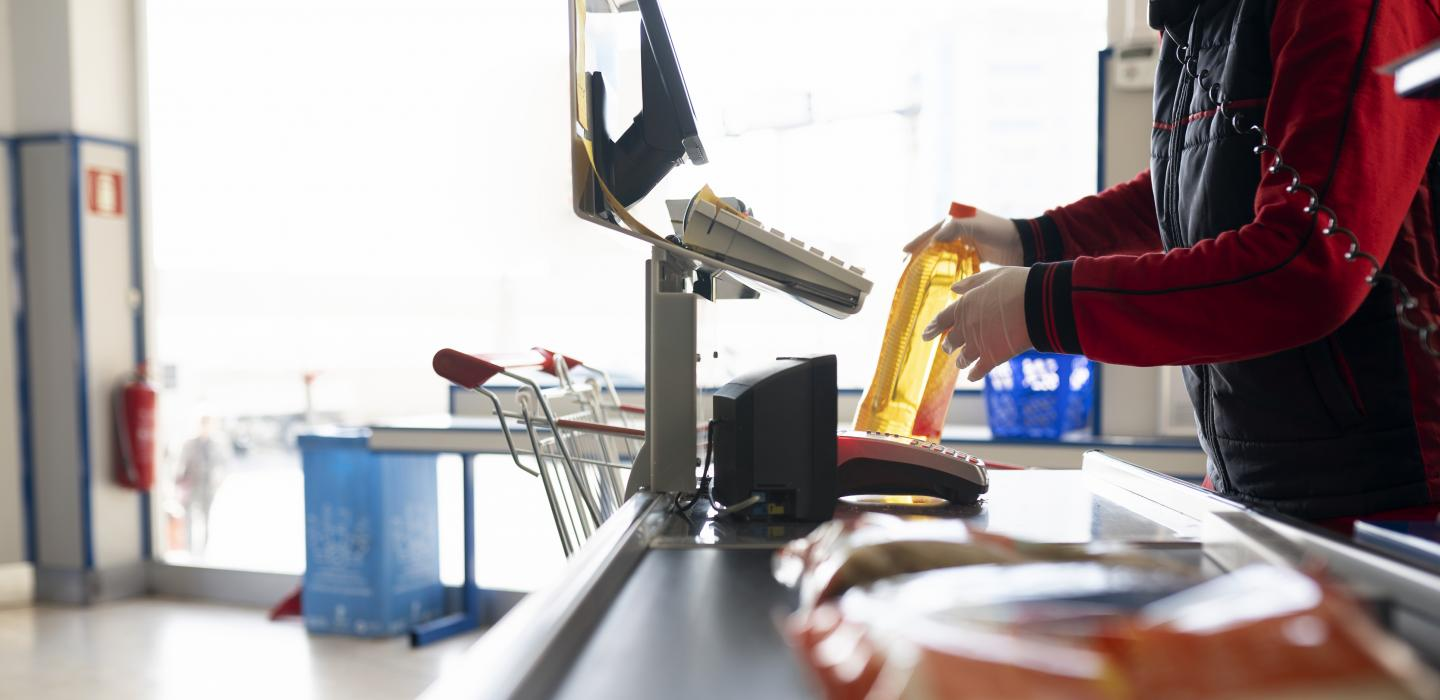 Close up of grocery clerk wearing gloves scanning items