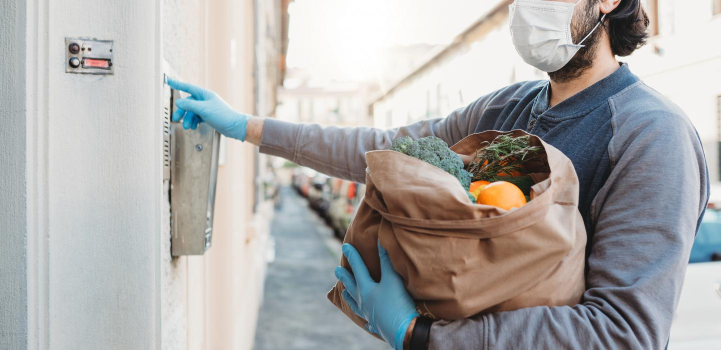 Person wearing gloves and mask delivers groceries