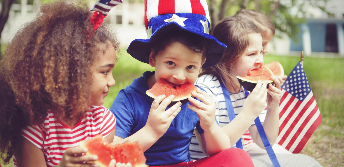 Kids eat watermelon at Fourth of July party