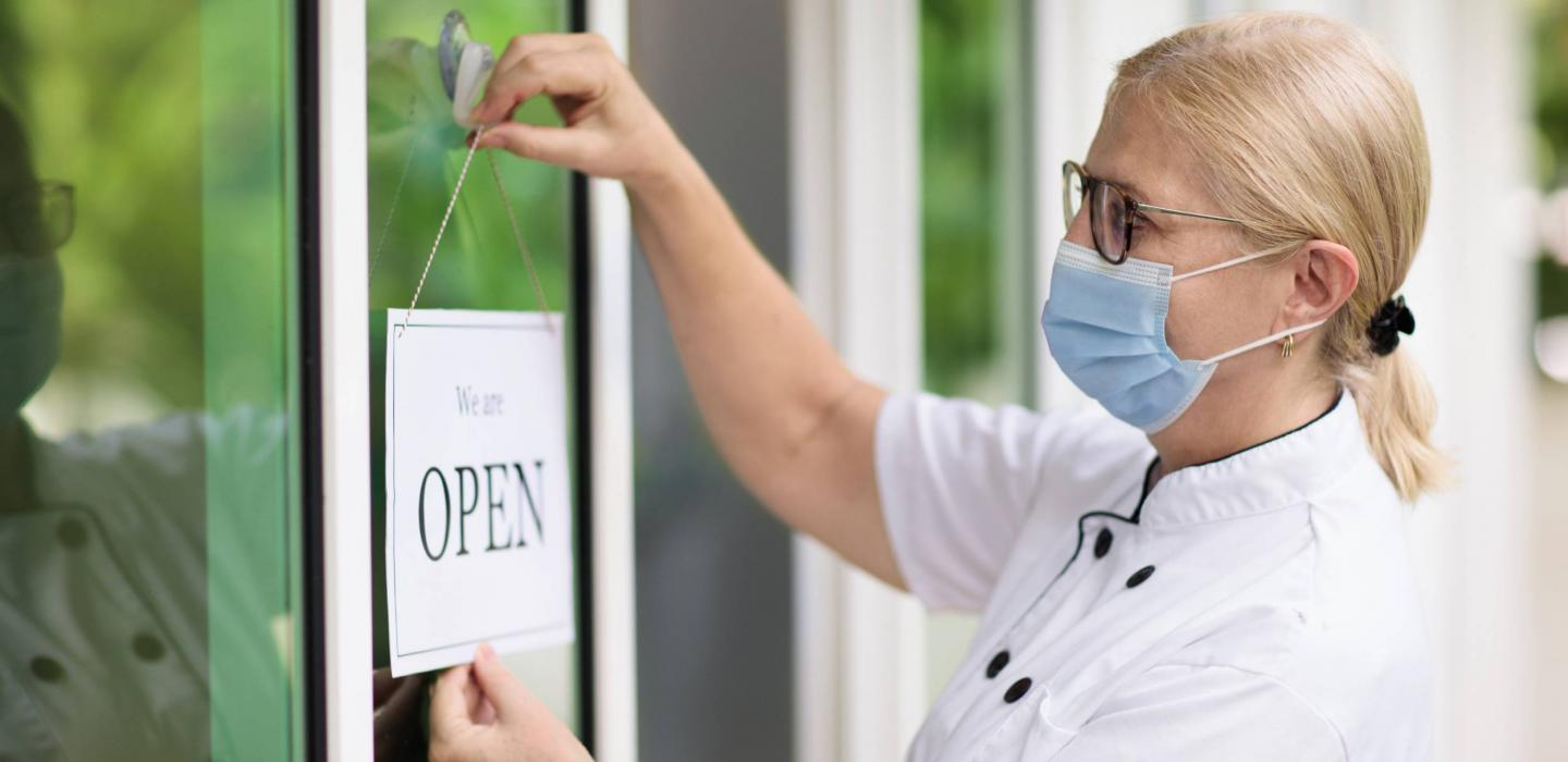 Woman wearing mask hands Open sign outside of shop