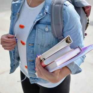 girl standing outside with a backpack and school books in her hands