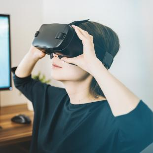 a woman has a headset on while viewing something via virtual reality