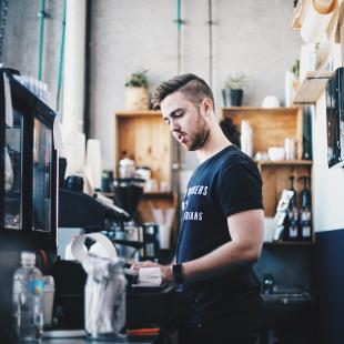 A guy is shown working at the cash register at a store in the daytime