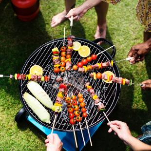 a grill showing people cooking skewers and other foods in the summer