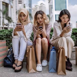 three girls sit on their phones with shopping bags after a long day of shopping
