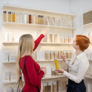 Two women are picking out colognes and perfumes at a makeup store