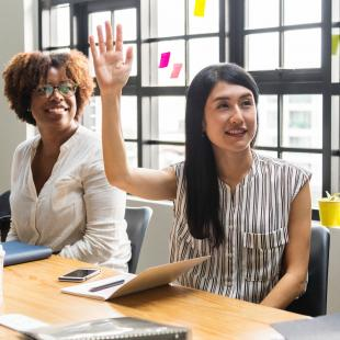 Woman raising her hand in a meeting