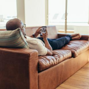 Man on couch using phone