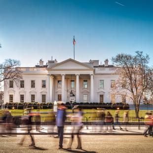 white house with people walking by