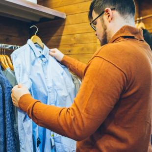 a guy contemplates whether he should purchase the light blue shirt or medium blue shirt