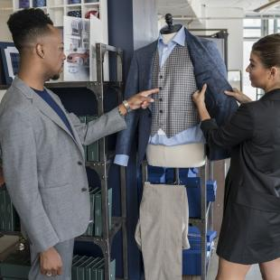 Customer and fashion store assistant choosing a suit