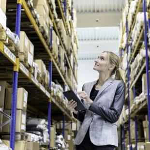 woman recording fulfillment delivery logistics in warehouse with boxes on shelves