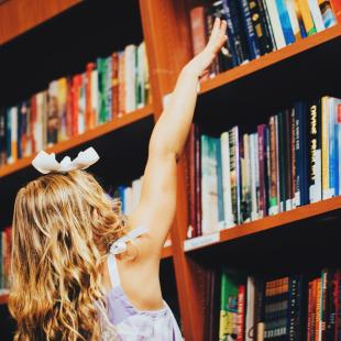 Little girl reaching for books on a shelf at Unclaimed Baggage Center