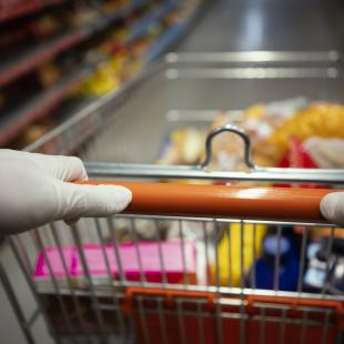 Woman wearing gloves pushes shopping cart