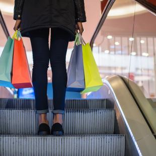 a woman is shown on the escalator with shopping bags