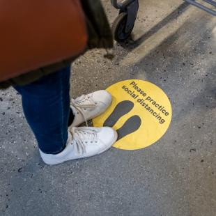 Person stands on social distancing sticker on the ground