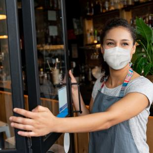 Woman opens shop doors wearing face mask