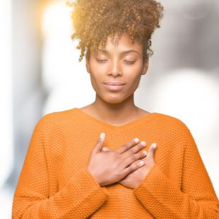Woman with hands over heart and eyes closed