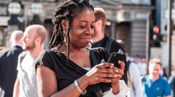 a woman looks down at her phone smiling