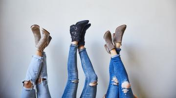three women with their legs up show off their shoes from DSW