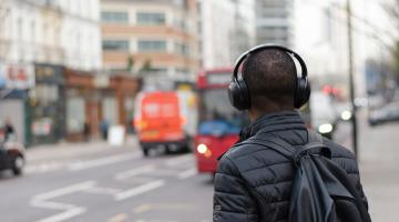 a guy stands on a busy city street with headphones on